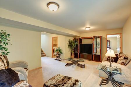 Acogedora habitación familiar en melocotón cálido y tonos beige. Cómodo sofá con otomana, TV con armarios y mesa de café de cristal. Noroeste, EE. UU. Foto de archivo