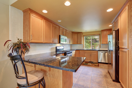 counter top: Maple kitchen cabinetry, granite counter top, steel appliances and tile floor. Kitchen room interior. Northwest, USA