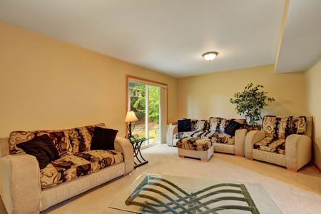 sofa set: Cozy family room in warm peach and beige tones. Comfortable sofa set with colorful cushions and modern glass coffee table. Doors to backyard. Northwest, USA