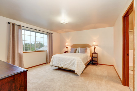 nightstands: Simple beige bedroom with minimal interior design. Double bed with headboard and two nightstands. Northwest, USA Stock Photo