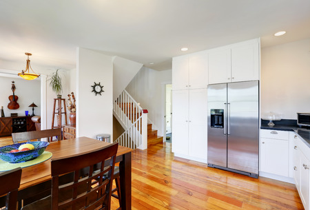 fridge: Design of kitchen room interior with white storage combination and built-in stainless steel fridge. Wooden dining table with chairs. Northwest, USA