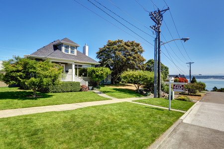 nicely: Single-family American craftsman house exterior. Blue sky background and nicely trimmed front yard. Northwest, USA