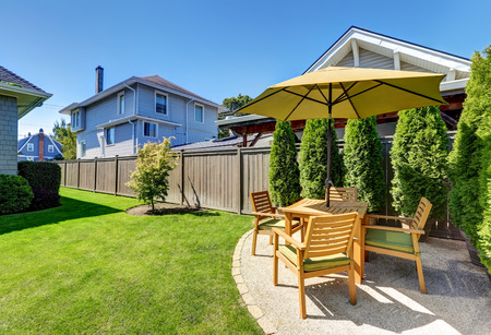 lawn area: American craftsman house exterior. Small Patio area with wooden table set and umbrella. Green thuja trees in pots and well kept lawn. Northwest, USA