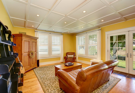 Cozy American sitting room with pastel yellow walls. Furnished with leather love seat, cabinet, coffee table and black book shelves. Northwest, USA