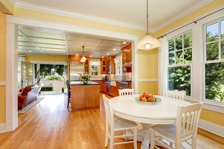 open plan: Open plan dining room interior. Yellow walls and hardwood floor. Kitchen and living room in the background. Open doors to the back yard. Northwest, USA