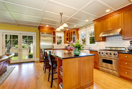 Design of brown wooden kitchen with steel appliances. Bar style kitchen island with fresh flowers and pendant lights. Northwest, USA