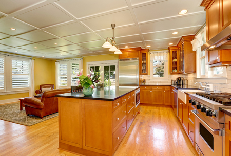 kitchen island: Design of brown wooden kitchen with steel appliances. Bar style kitchen island with fresh flowers and pendant lights. Family room in the background. Northwest, USA