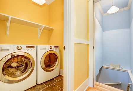 dryer  estate: White Modern appliances in small yellow laundry room with open door. Staircase to the basement. Northwest, USA