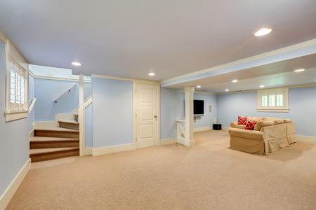 Spacious basement room interior in pastel blue tones. Beige carpet floor and large corner sofa with TV. Northwest, USA