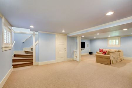 basement: Spacious basement room interior in pastel blue tones. Beige carpet floor and large corner sofa with TV. Northwest, USA