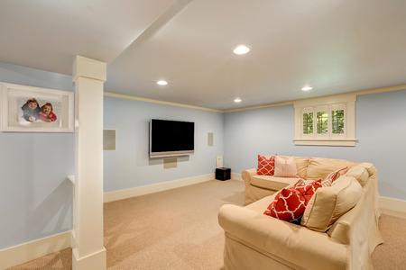 Spacious basement living room interior in pastel blue tones. Beige carpet floor and large corner sofa with TV. Northwest, USA Foto de archivo