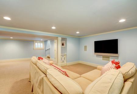 Ruime kelder woonkamer interieur in pastel blauw tinten. Beige vloerbedekking en een grote hoekbank met TV. Northwest, USA Stockfoto