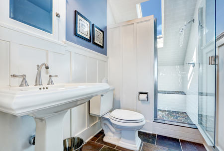 upstairs: Refreshing blue bathroom design with stone tile floor. Upstairs interior with vaulted ceiling and skylight. Northwest, USA