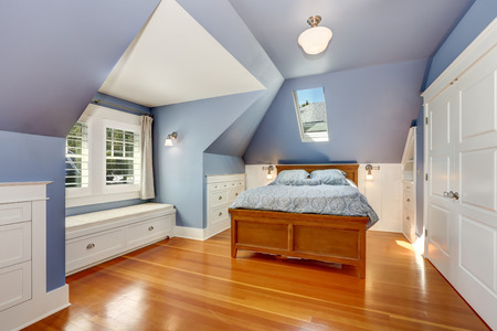 Lavender interior of attic bedroom with queen size bed and hardwood floor. Also window seat and built-in cabinets. Northwest, USA Stockfoto