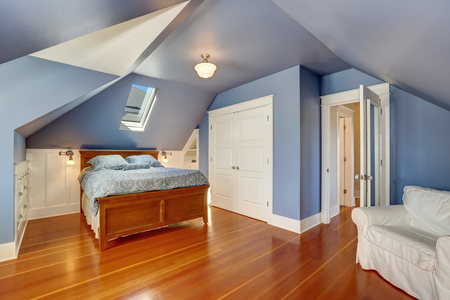 attic: Lavender interior of attic bedroom with queen size bed and hardwood floor. Also white doors closet and built-in cabinets. Northwest, USA Stock Photo