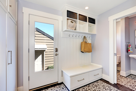 storage units: White hallway storage cabinet with hangers, bench with drawers and storage units on the top. And door to the bathroom . Northwest, USA Stock Photo