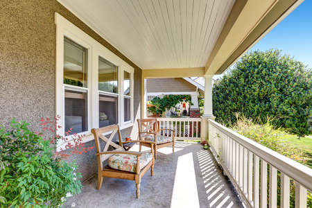 Front covered porch with outdoor furniture overlooking neighborhood. Northwest, USA