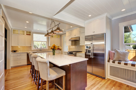 fridge: White interior of kitchen room with bar style kitchen island and stools, stainless steel double fridge and view of window seat. Northwest, USA