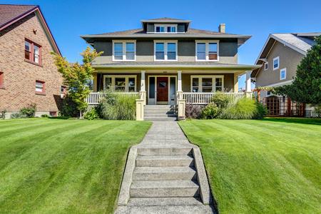 Agradable atractivo exterior de la casa de estilo artesano americano. Vista porche columna y césped bien cuidado en la parte delantera. Noroeste, EE.UU. Foto de archivo