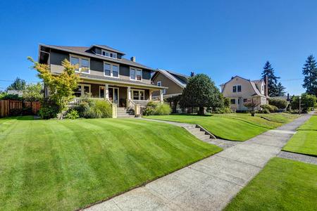 Mooie beteugelen beroep van de Amerikaanse ambachtsman stijl huis. Column veranda uitzicht en vers gemaaid gazon. Northwest, USA Stockfoto