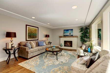 Cozy living room interior with hardwood floor and fireplace. Furnished with mocha colored sofa, vintage lounge Chairs and round glass top coffee table on a rug. Northwest, USA