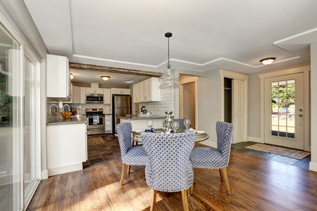 Dining area with blue chairs and table setting. And view of kitchen room. Northwest, USA