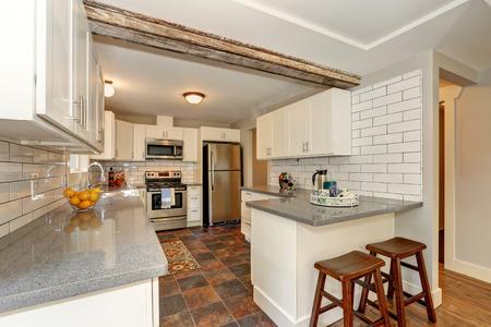 シンプルで実用的なキッチン インテリア白いモダンなキャビネット、灰色花崗岩のカウンター トップ、石タイルの床。米国北西部 写真素材