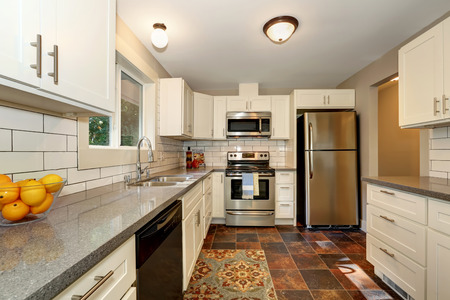 cabinets: Simple yet practical kitchen interior with white modern cabinets, grey granite counter top and stone tile flooring. Northwest, USA