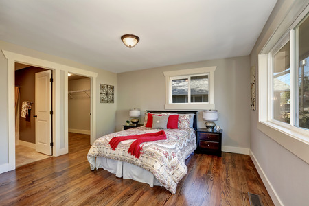 View of tidy bedroom with hardwood floor and colorful bed with red pillows. Has doors to the bathroom and empty closet. Northwest, USA
