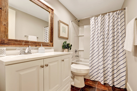 White tones Bathroom with vanity cabinet and wooden framed mirror. Decorated with picture, plant pot and striped curtain. Northwest, USA Stock Photo