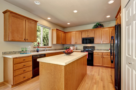 American classic cream colored luxury kitchen with fitted black appliances and large kitchen island. Northwest, USA