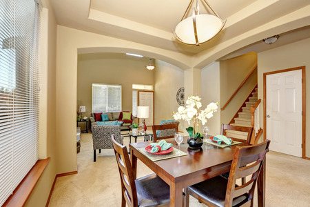 Open floor plan. Dining area and living room with entryway. Creamy tones interior of luxury house. Wooden table set view with four chairs and nice decor. Northwest, USA