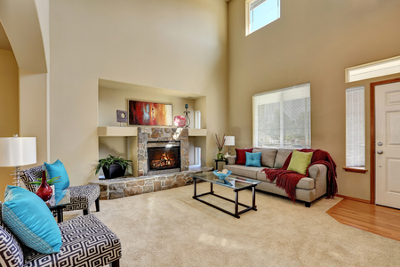 stone fireplace: Cozy luxury family room with high ceiling and entryway. Stone fireplace with niche, armless accent chairs with geometric print and blue pillows. Northwest, USA Stock Photo