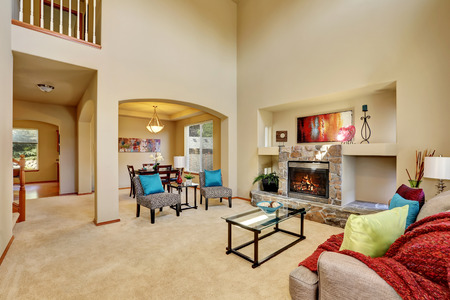 Cozy luxury family room with high ceiling and arched doorway. Stone fireplace with niche, armless accent chairs with geometric print and blue pillows. Northwest, USA