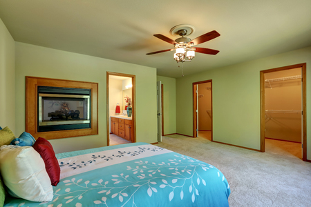 Large and simple green bedroom interior with walk through closet, wall mounted electric fireplace. Nice bed with blue bedding and colorful pillows. Northwest, USA