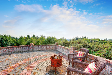 fire pit: Paved brick patio of luxury house on Blue sky background. Two wicker chairs with  bright pink pillows and fire pit. Northwest, USA