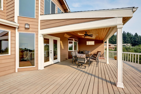 deck: Large wooden walkout deck with flat roof extension and comfortable seating arrangement. Northwest, USA Stock Photo