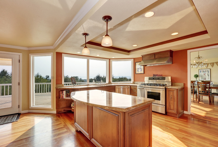 northwest: Photo of open concept kitchen with cabinets, granite countertops, hardwood floors and an island. Window view. Northwest, USA Stock Photo