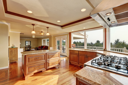 renovated: Photo of open concept kitchen with cabinets, granite countertops, hardwood floors and an island. Window view. Northwest, USA Stock Photo