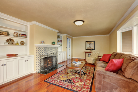Craftsman-style family room with built-in bookcases, fireplace with tile surround and persian red rug. Northwest, USA