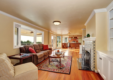 Craftsman-style family room with brown sofa and fireplace with tile surround, persian red rug. Northwest, USA