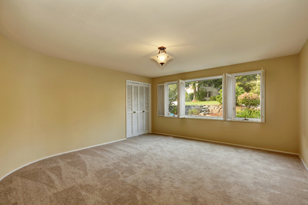 remodeled: Empty room in beige and yellow colors with open windows. Carpet floor and closet. Northwest, USA
