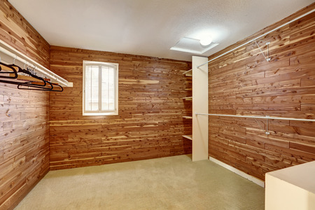 Empty walk-in closet with wooden walls and carpet floor. Northwest, USA