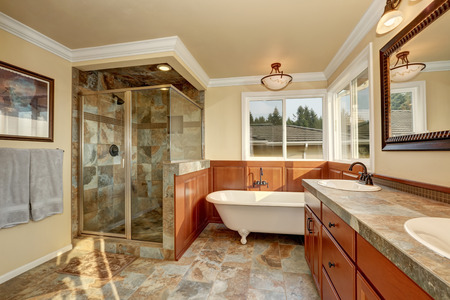 Bathroom with natural stone tile and beige walls. Glass corner shower, freestanding white tub and double sink vanity bathroom. Northwest, USA