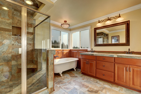 Bathroom with beige tile trim and glass shower. Wooden cabinet with vessel sinks and mirror. Northwest, USA
