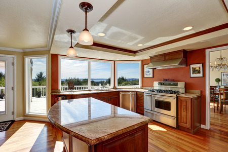 countertops: Photo of open concept kitchen with cabinets, granite countertops, hardwood floors and an island. Window view. Northwest, USA Stock Photo