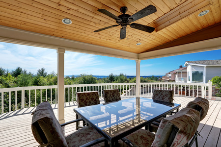 Large wooden walkout deck with flat roof extension and comfortable seating arrangement. Northwest, USA Stock Photo