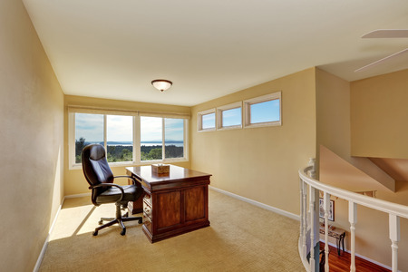 upstairs: Upstairs home office interior design in yellow tones with nice wooden desk and carpet floor. Northwest, USA