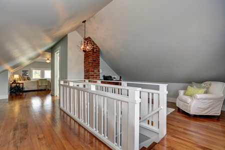 Interior of upstairs room with hardwood floor and vaulted ceiling. White railings staircase and cozy sitting area. Northwest, USA