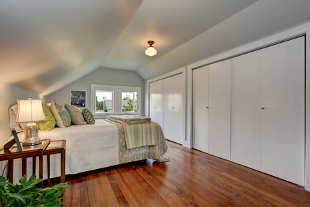 attic: Attic bedroom interior with vaulted ceiling and hardwood floor. Built-in closets with white doors. Northwest, USA